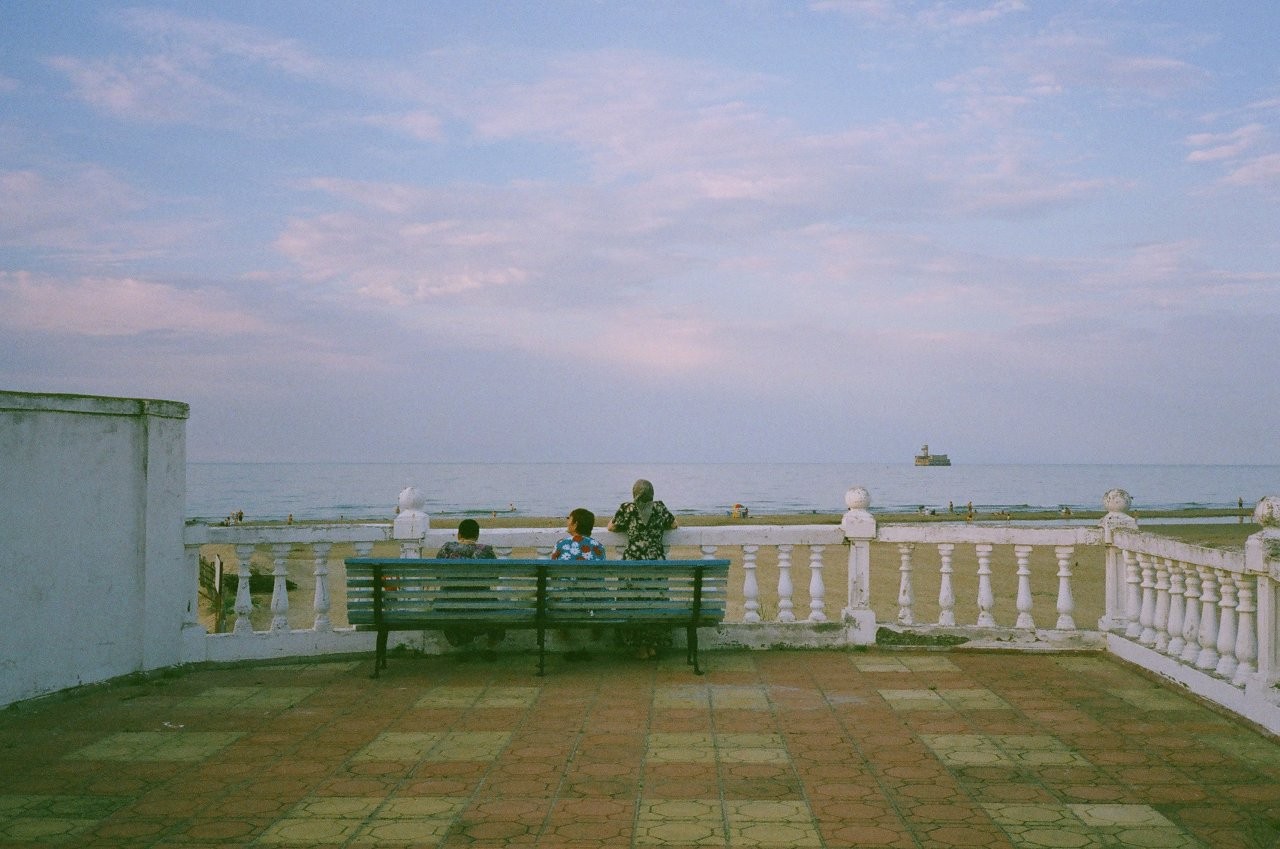 Женщины на побережье Каспийска слушают лезгинку. На фоне виден восьмой цех завода «Дагдизель», на котором испытывали военную ракетную технику