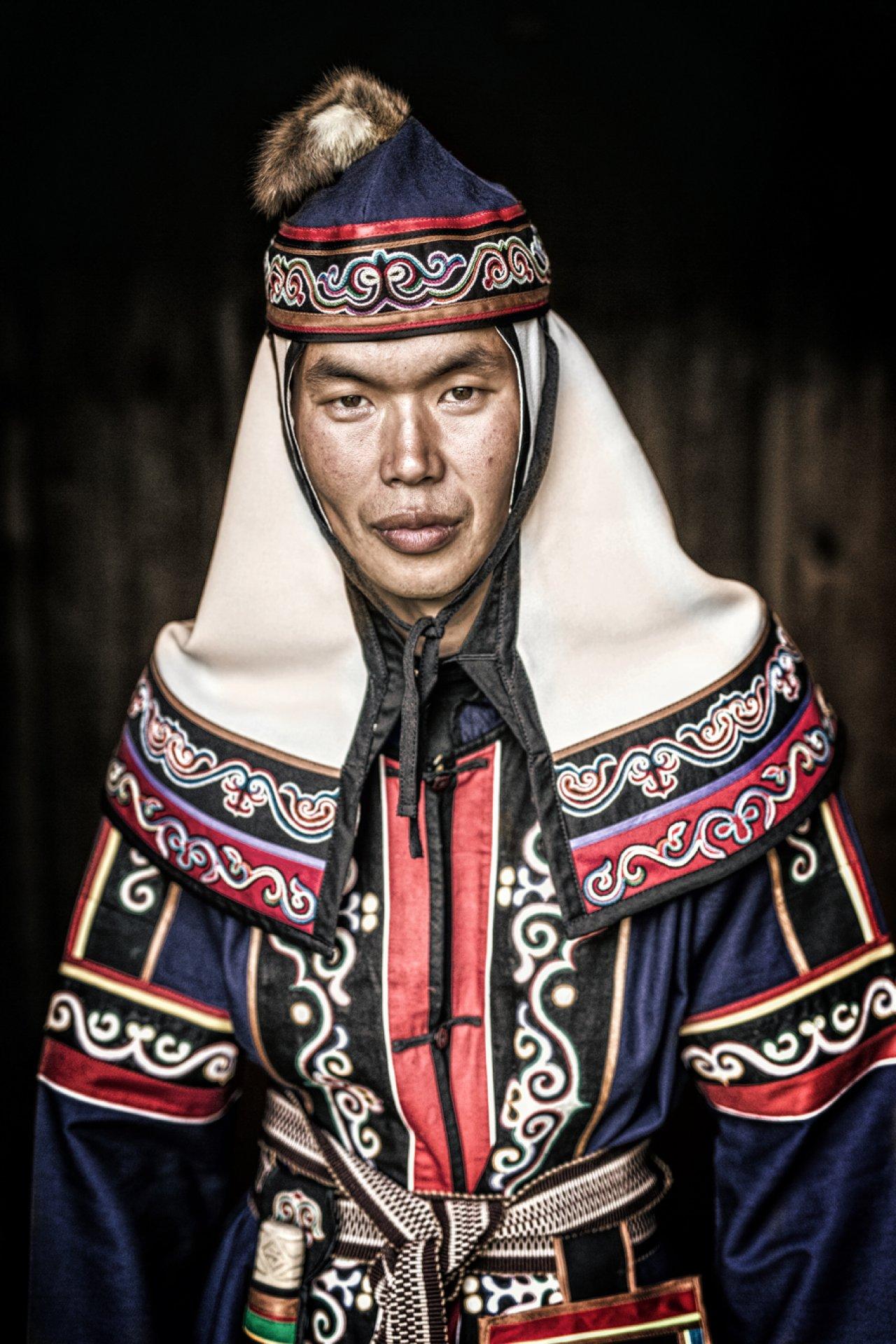 Этот молодой человек — представитель народа ульчи, Он живёт в посёлке Булава, в 757 километрах от Хабаровска. Традиционная одежда уличей — халат покроя кимоно. Зимой одежду утепляют ватой. Фото: © Alexander Khimushin / The World In Faces